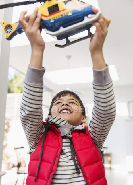 Happy boy playing with toy helicopter — Stock Photo