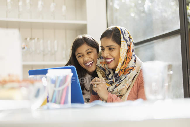 Happy mother in hijab and daughter using laptop — Stock Photo
