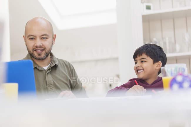 Батько і син за допомогою ноутбука і фарбування за столом — стокове фото
