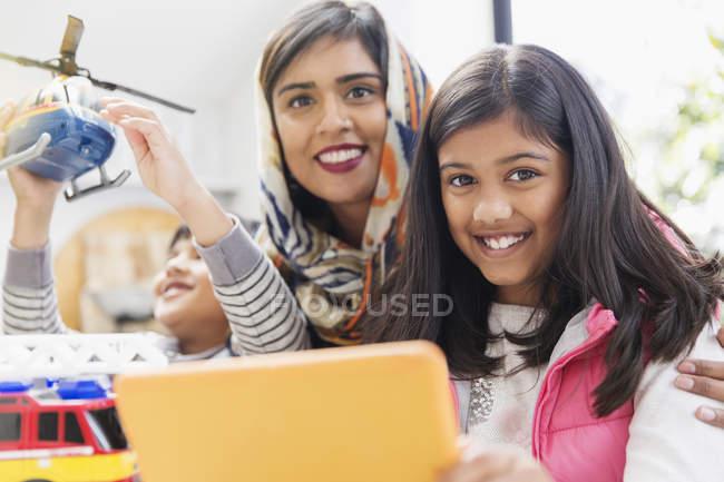 Retrato madre feliz y los niños jugando y utilizando la tableta digital - foto de stock