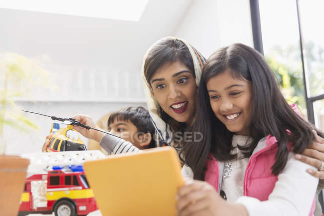 Happy mother and daughter using digital tablet — Stock Photo