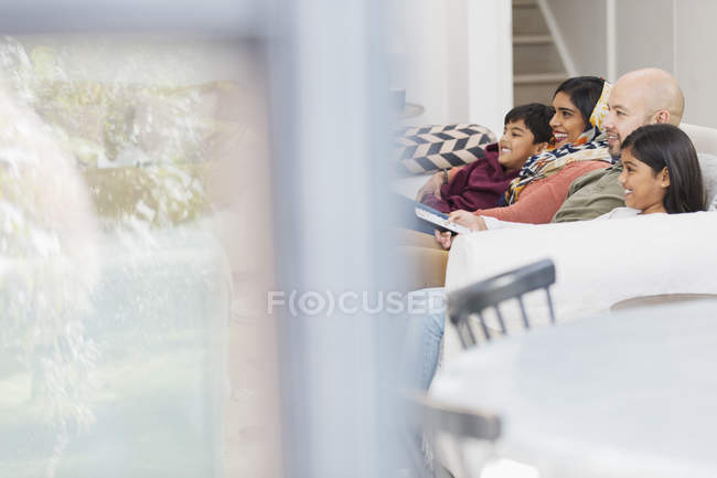 Family watching TV on living room sofa — Stock Photo