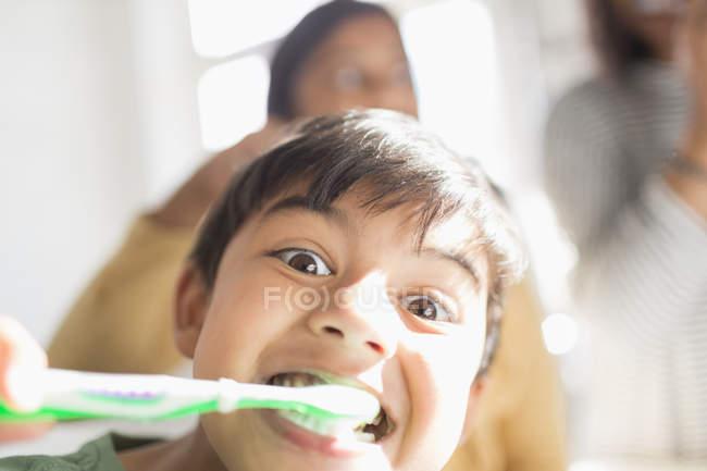 Portrait playful, silly boy brushing teeth — Stock Photo