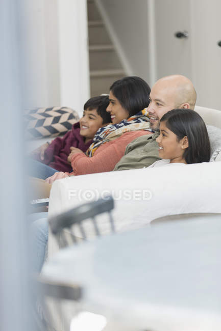 Family watching TV on living room sofa — Stock Photo