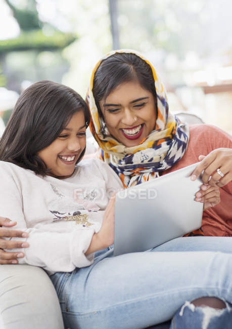 Laughing, happy mother in hijab and daughter using digital tablet — Stock Photo