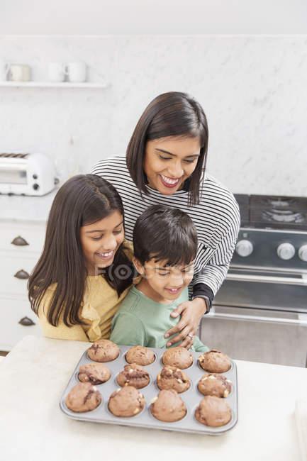 Matriz e crianças que cozem muffins do chocolate na cozinha — Fotografia de Stock