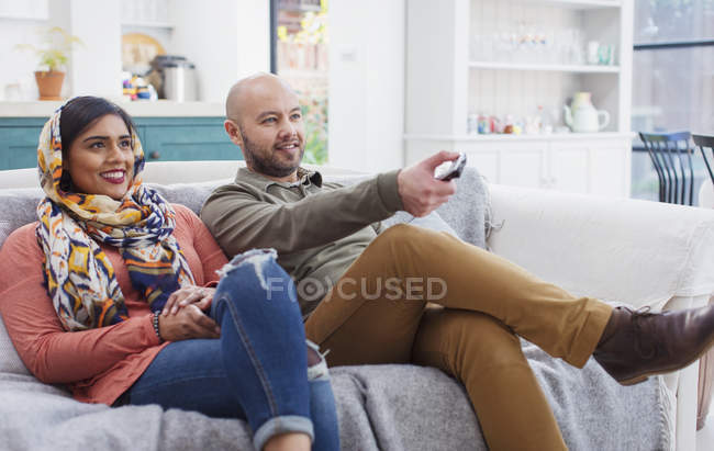 Couple watching TV on living room sofa — Stock Photo