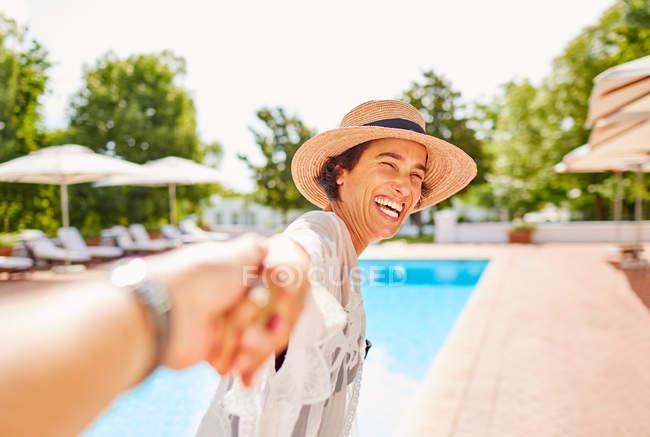 Щаслива дружина ведучи чоловіка рукою в сонячному курорті біля басейну — стокове фото