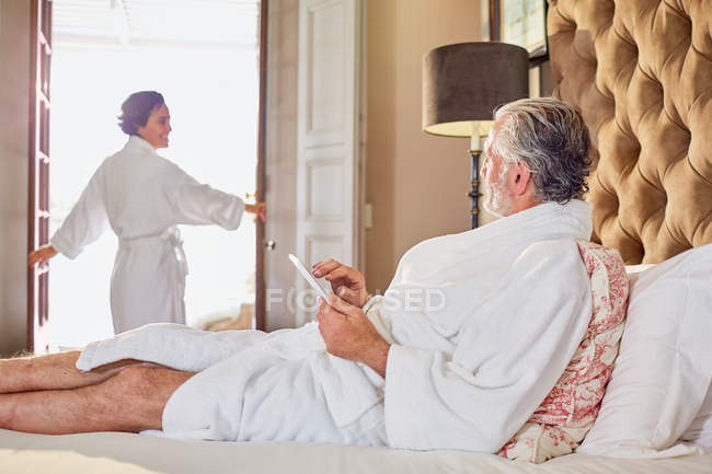 Mature couple in bathrobes relaxing in hotel room — Stock Photo