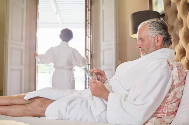 Взрослый человек в спа-халат с использованием цифрового планшета на кровати отеля — стоковое фото