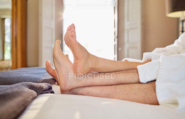 Barefoot couple relaxing on hotel bed — Stock Photo