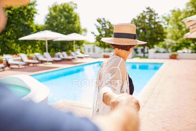 Couples matures retenant des mains à la piscine ensoleillée — Photo de stock