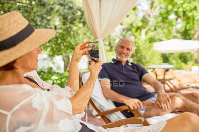 Wife with camera phone photographing husband at resort poolside — Stock Photo