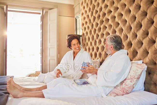 Пожилая пара в халате на кровати отеля — стоковое фото