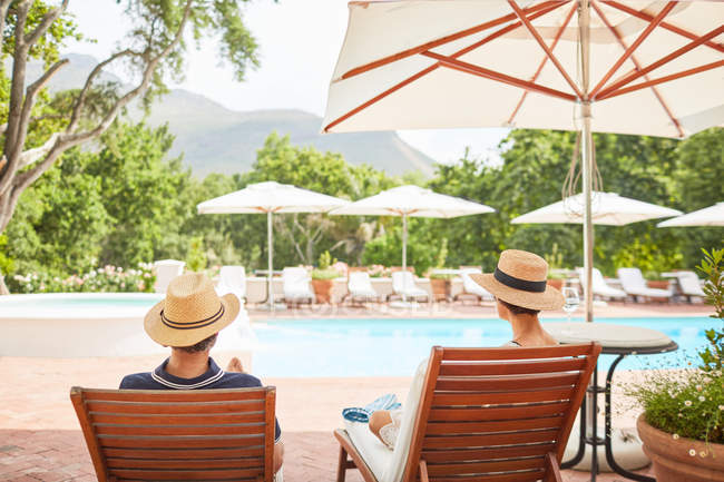 Couple relaxing on lounge chairs at sunny resort poolside — Stock Photo