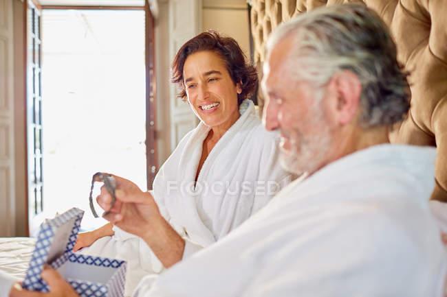 Дружина дає наручні годинники до чоловіка на готельному ліжку — стокове фото