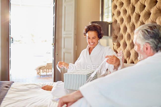 Чоловік дивиться щаслива дружина відкриття подарунка на готельному ліжку — стокове фото