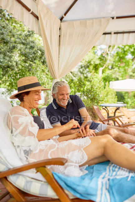 Mature couple using smart phone in cabana at resort poolside — Stock Photo