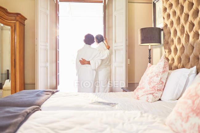 Пара в спа халаты стоя на дверях отеля Балкон — стоковое фото