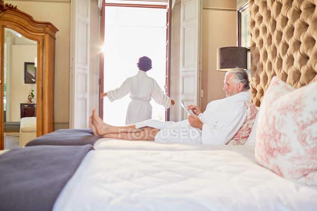 Пожилая пара в халате, отдыхая в спальне отеля — стоковое фото