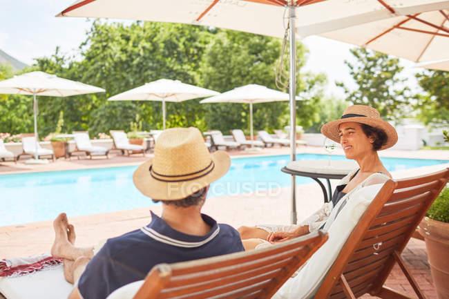 Coppia rilassante su sedie a sdraio al Resort a bordo piscina — Foto stock