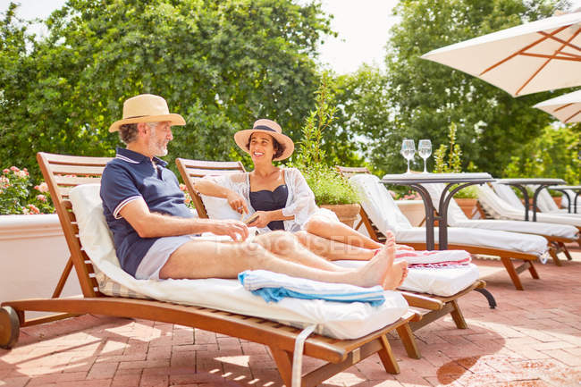 Mature couple relaxing on lounge chairs at sunny poolside — Stock Photo