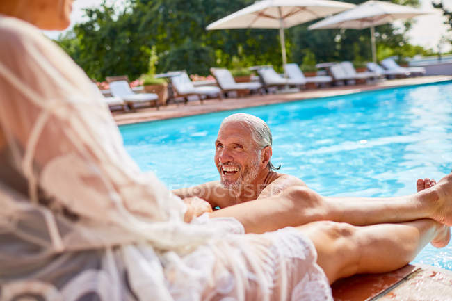 Happy couple relaxing at sunny resort swimming pool — Stock Photo