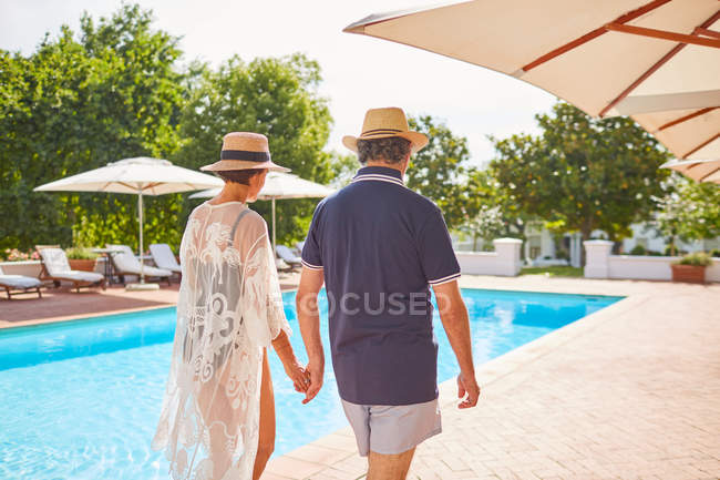 Mature couple holding hands, walking along sunny resort swimming pool — Stock Photo