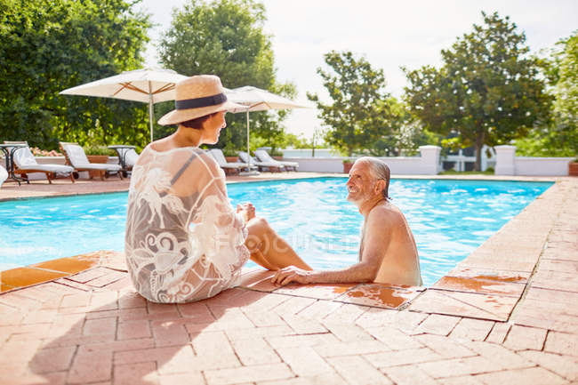 Happy mature couple relaxing at sunny resort swimming pool — Stock Photo