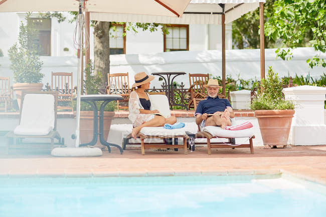 Mature couple relaxing on lounge chairs at resort poolside — Stock Photo