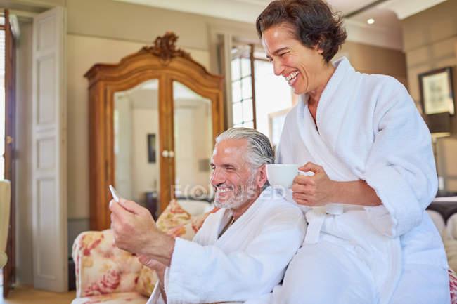 Счастливая Пожилая пара в спа-халаты, попивая кофе в гостиничном номере — стоковое фото
