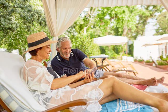 Зріла пара відпочинку, використання смарт-телефон на шезлонгах в курортному Cabana — стокове фото