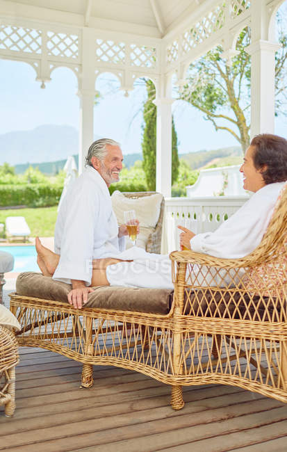 Mature couple in bathrobes relaxing, drinking champagne in resort gazebo — Stock Photo