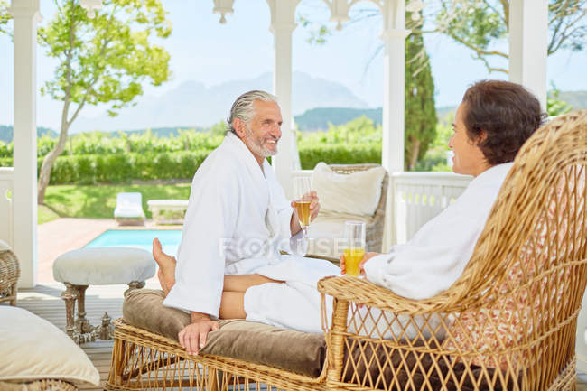 Mature couple in bathrobes relaxing, drinking mimosas in resort gazebo — Stock Photo