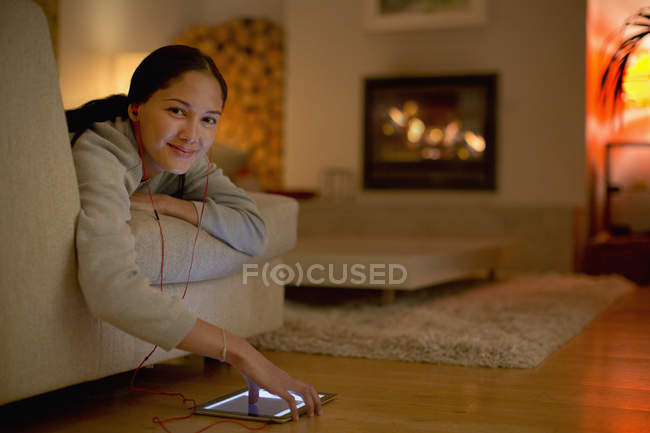 Portrait smiling young woman listening to music with headphones and digital tablet — Stock Photo