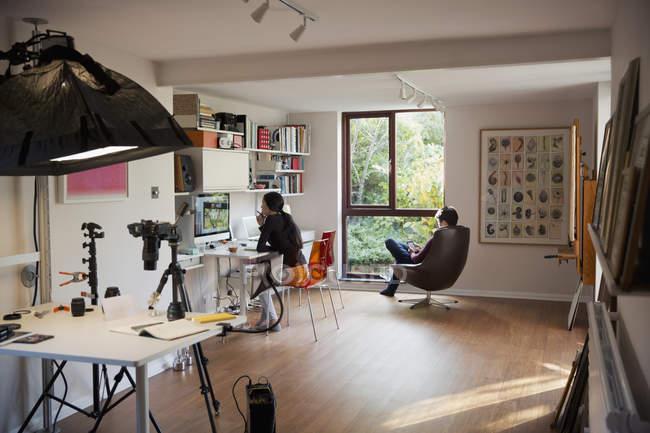 Pares que trabalham e que lêem no escritório home — Fotografia de Stock