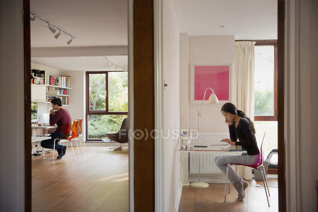 Couple working in bedroom and home office — Photo de stock