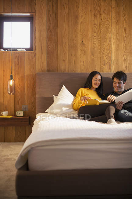 Couple reading book and using digital tablet in bed — Stock Photo