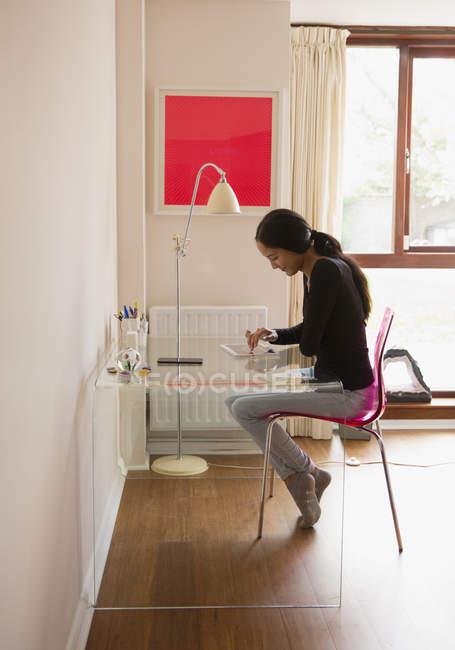 Jovem mulher usando tablet digital na mesa — Fotografia de Stock