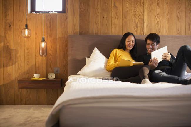 Paar liest Buch und nutzt digitales Tablet im Bett — Stockfoto