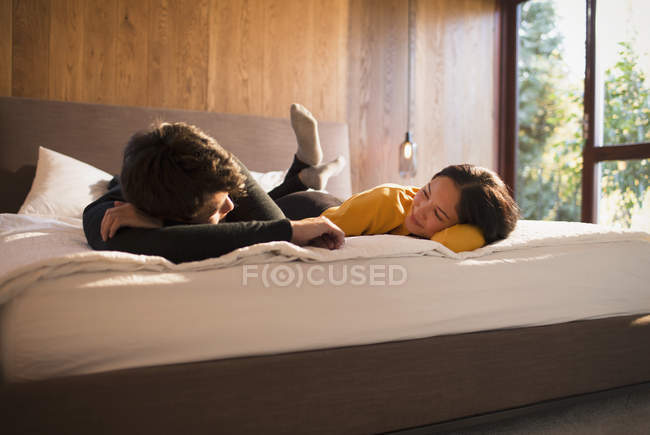 Couple laying on bed talking — Stock Photo