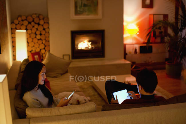 Couple using digital tablet and smart phone in living room — Stock Photo