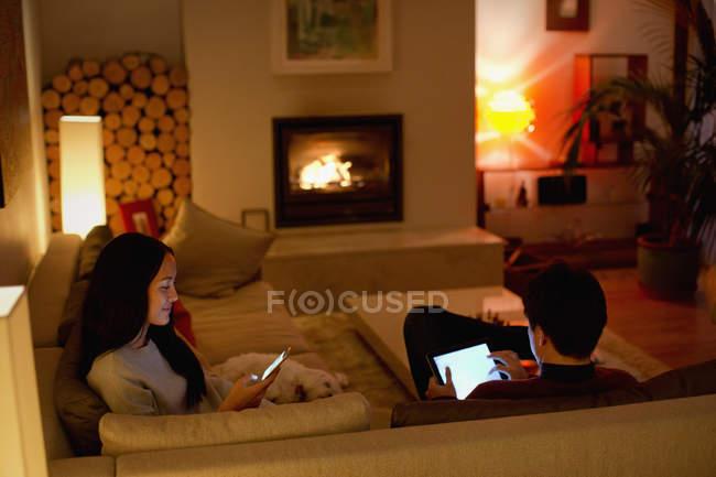 Pares que usam a tabuleta digital e o telefone esperto na sala de visitas — Fotografia de Stock