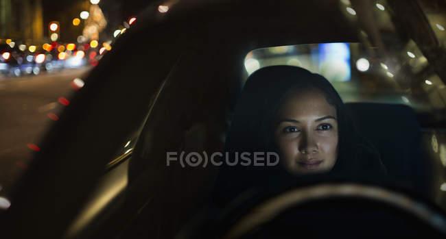 Young woman driving car at night — Stock Photo