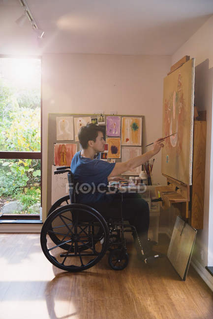 Male artist in wheelchair painting in art studio — Stock Photo