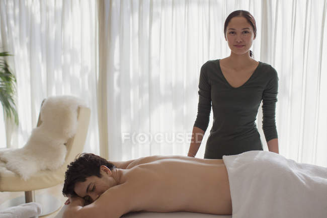 Portrait confident female masseuse giving man massage — Stock Photo