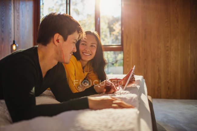 Посміхаючись пара з навушниками обмін цифровий планшет в ліжку — стокове фото