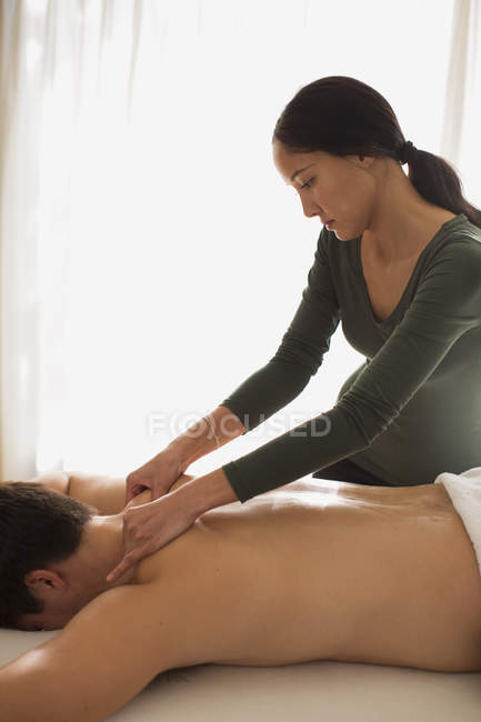 Female masseuse giving man massage — Stock Photo