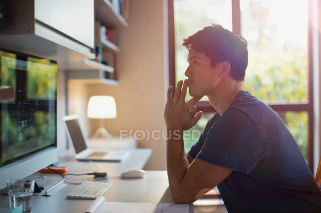 Thoughtful man working at computer in home office — Stock Photo