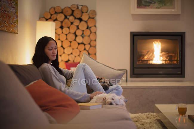 Молодая женщина, расслабляясь на диване с собаками на камине — стоковое фото
